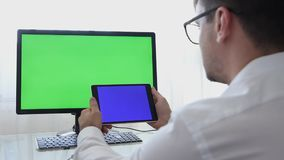 LOS ANGELES, CALIFORNIA - JUNE 3, 2019: Engineer, Constructor, Designer in Glasses Working on a Personal Computer with a. Green Screen on Monitor which has stock video