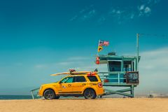 Los Angeles/California/USA - 07 22 2013: Leibwächterturm auf dem Strand mit gelbem Auto nahe bei ihm Stockbild