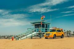 Los Angeles/California/USA - 07 22 2013: Leibwächterturm auf dem Strand mit gelbem Auto nahe bei ihm stockbilder