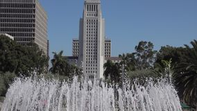 Los Angeles city hall tilt-up from grand park fountain. The Los Angeles city hall building is shown in a tilt-up view from the decorative water fountain in stock video footage