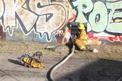 Los Angeles Junk Yard Fire 2016 Firemen With Hose. Los Angeles ~2016 ~ Firemen Cutting Into Wall To Gain Access To Fire royalty free stock photo