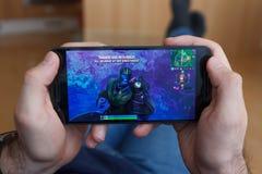 LOS ANGELES KALIFORNIA, CZERWIEC, - 3, 2019: Łgarski mężczyzna trzyma smartphone i bawić się Fortnite mścicieli: Endgame gra na fotografia stock