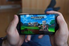 LOS ANGELES KALIFORNIA, CZERWIEC, - 3, 2019: Łgarski mężczyzna trzyma smartphone i bawić się Minecraft grę na smartphone ekranie  zdjęcia stock