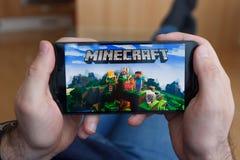 LOS ANGELES KALIFORNIA, CZERWIEC, - 3, 2019: Łgarski mężczyzna trzyma smartphone i bawić się Minecraft grę na smartphone ekranie  obraz royalty free