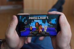 LOS ANGELES KALIFORNIA, CZERWIEC, - 3, 2019: Łgarski mężczyzna trzyma smartphone i bawić się Minecraft grę na smartphone ekranie  zdjęcie stock