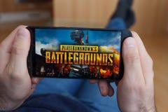 LOS ANGELES KALIFORNIA, CZERWIEC, - 3, 2019: Łgarski mężczyzna trzyma smartphone i bawić się PlayerUnknown s polych bitw PUBG grę obrazy stock