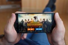 LOS ANGELES KALIFORNIA, CZERWIEC, - 3, 2019: Łgarski mężczyzna trzyma smartphone i bawić się PlayerUnknown s polych bitw PUBG grę fotografia stock