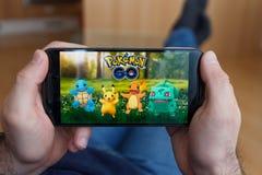 LOS ANGELES KALIFORNIA, CZERWIEC, - 3, 2019: Łgarski mężczyzna trzyma smartphone i bawić się Pokemon Iść gra na smartphone ekrani obraz stock