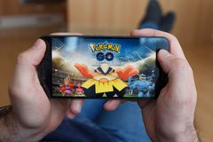 LOS ANGELES KALIFORNIA, CZERWIEC, - 3, 2019: Łgarski mężczyzna trzyma smartphone i bawić się Pokemon Iść gra na smartphone ekrani obrazy stock