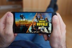 LOS ANGELES KALIFORNIA, CZERWIEC, - 3, 2019: Łgarski mężczyzna trzyma smartphone i porównuje PUBG i battle royale gry na smartpho obraz stock