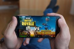 LOS ANGELES KALIFORNIA, CZERWIEC, - 3, 2019: Łgarski mężczyzna trzyma smartphone i porównuje PUBG i battle royale gry na smartpho obraz royalty free