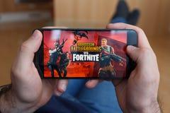 LOS ANGELES KALIFORNIA, CZERWIEC, - 3, 2019: Łgarski mężczyzna trzyma smartphone i porównuje PUBG i Fortnite gry na smartphone obrazy royalty free