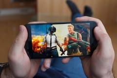 LOS ANGELES KALIFORNIA, CZERWIEC, - 3, 2019: Łgarski mężczyzna trzyma smartphone i porównuje PUBG i Fortnite gry na smartphone fotografia royalty free