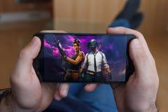 LOS ANGELES KALIFORNIA, CZERWIEC, - 3, 2019: Łgarski mężczyzna trzyma smartphone i porównuje PUBG i Fortnite gry na smartphone zdjęcie stock