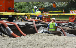Los Angeles Sinkhole. Los Angeles, CA, - July 30, 2014: City workers work in a sink hole to repair a 93 year old water main which ruptured July 29, 2014 spilling Royalty Free Stock Photography