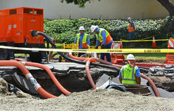 Los Angeles Sinkhole. Los Angeles, CA, - July 30, 2014: City workers work in a sink hole to repair a 93 year old water main which ruptured July 29, 2014 spilling Royalty Free Stock Photos