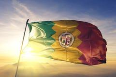 Los Angeles-Stadt des Flaggentextilstoffgewebes Vereinigter Staaten, das auf den Spitzensonnenaufgangnebelnebel wellenartig beweg lizenzfreies stockfoto