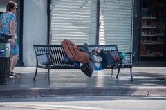 LOS ANGELES USA - AUGUSTI 1, 2014 - hemlös som sover på en bänk på Walk av berömmelse royaltyfri foto