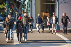 Los Angeles, USA - December 25, 2015: Pedestrians crossing the famous Santa Monica boulevard during winter bundled up with coats Stock Photos