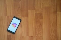 Instagram on smartphone screen. Los Angeles, USA, july 18, 2017: Instagram on smartphone screen placed on the laptop on wooden background Stock Image