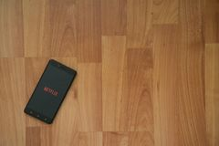 Netflix on smartphone screen. Los Angeles, USA, july 18, 2017: Netflix on smartphone screen placed on the laptop on wooden background Royalty Free Stock Photos
