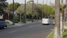 Los Angeles, USA, March 2019: Aerial video of U.S. Postal vehicle and postman deliver mail in Eagle Rock, Los Angeles stock footage