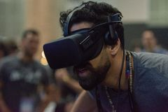A man plays a video game using virtual reality glasses. Los Angeles, USA - May 5, 2018: A man plays a video game using virtual reality glasses during VRLA stock photo