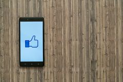 Facebook like logo on smartphone screen on wooden background. Los Angeles, USA, november 7, 2017: Facebook like logo on smartphone screen on wooden background Stock Image