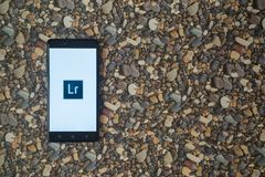 Adobe photoshop lightroom logo on smartphone on background of small stones stock image