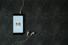 Gmail logo on smartphone screen. Los Angeles, USA, october 23, 2017: Gmail logo on smartphone screen and earphones plugged in on metal plate background Stock Image