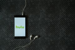 Hulu logo on smartphone screen. Los Angeles, USA, october 23, 2017: Hulu logo on smartphone screen and earphones plugged in on metal plate background Stock Photos