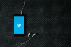 Twitter logo on smartphone screen. Los Angeles, USA, october 23, 2017: Twitter logo on smartphone screen and earphones plugged in on metal plate background Royalty Free Stock Photos