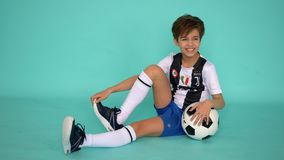 Los Angelos, Californië, de V.S. - 20 Februari, 2019: knap jongensvoetbal met voetbalbal die en op groen glimlachen stellen stock videobeelden