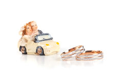 Los anillos de bodas al lado de un chocolate del juguete trabajan a máquina el aislamiento en un whi Imagenes de archivo