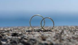 Los anillos de bodas colocaron en una roca imagen de archivo