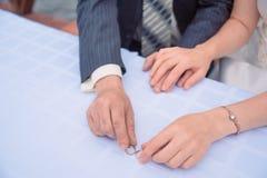 Los anillos de bodas del oro mienten en la tabla detrás de ellos empañaron las manos de los recienes casados Mano de la novia con Imagenes de archivo