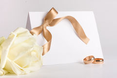 Los anillos de bodas e invitan con se levantaron Imagenes de archivo
