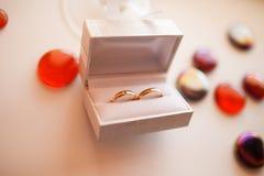 Los anillos de bodas en la caja blanca mienten en una tabla rodeada por decorati Imagen de archivo
