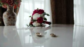 Los anillos de bodas giratorios acercan al ramo en el piano metrajes