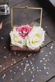 Los anillos de bodas de la novia y del novio están en una caja de cristal en las rosas, la caja están en la tabla de madera en el fotos de archivo