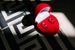 Los anillos de bodas mienten en una caja en forma de corazón roja fotos de archivo