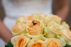 Los anillos de bodas de oro mienten en un brote de la rosa del amarillo Mentira de los anillos de bodas en un brote de flor Fotografía de archivo
