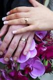 Los anillos de bodas y entregan el ramo nupcial Foto de archivo libre de regalías