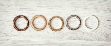 Los anillos de las mujeres arreglaron en fila en el backround de madera Foto de archivo