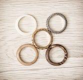Los anillos de las mujeres dispuestos en el fondo de madera Foto de archivo