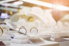 Los anillos y los collares de diamante de la joyería muestran en tienda al por menor de lujo Foto de archivo libre de regalías