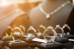 Los anillos y los collares de diamante de la joyería muestran en tienda al por menor de lujo imágenes de archivo libres de regalías