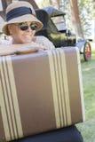 los años 20 vistieron a la muchacha con la maleta cerca del coche del vintage Imagen de archivo libre de regalías