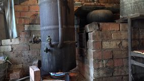 Los aparatos de la destilación del alcohol en la llama y el hombre llevan el tarro con alcohol 4K almacen de video