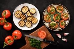 Los aperitivos asaron a la parrilla las berenjenas con los tomates, el ajo y el eneldo imagen de archivo libre de regalías